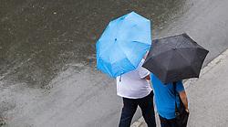 THEMENBILD - zwei Personen spazieren bei Regen mit ihren Regenschirmen auf der Strasse, aufgenommen am 11.08.2014 in Kaprun, Österreich // two people walk in the rain on the street with their umbrellas, Kaprun, Austria on 2014/08/11. EXPA Pictures © 2014, PhotoCredit: EXPA/ JFK