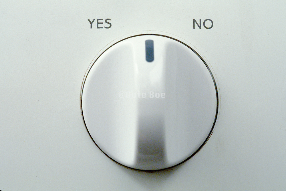 detail of washing machine knob set to between yes and no