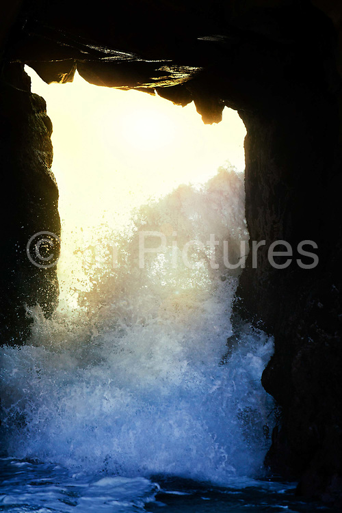 Waves break through the natural arch of a large rock formation at beach on Pacific ocean coast near Big Sur with sun shining through