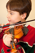 Boy age seven practicing violin at music lesson. St Paul Minnesota USA