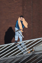 © Licensed to London News Pictures . 14/09/2015. Manchester, UK. An inmate at HMP Manchester ( Strangeways Prison ) , identified locally as STUART HORNER , smashes skylights with a piece of metal after climbing a fence and on to the roof , in protest of conditions inside . Photo credit : Joel Goodman/LNP