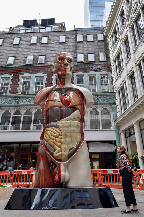 """© Licensed to London News Pictures. 24/06/2017. London, UK. A member of the public views a 21 feet tall, 2.5 tonne bronze sculpture called """"Temple"""" by Damien Hirst that has been unveiled near the Lloyds Building in the City of London.  The artwork will be on display as part of """"Sculpture in the City"""", a festival of sculpture in the City of London showing works by leading artists. Photo credit : Stephen Chung/LNP"""