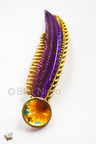 """Sunflower Accent hairpiece/ accessory Designed and handmade photo jewelry by Star. <br /> This can be worn as a hairpiece/ accessory that can also be clipped  to a blouse,pocket book,hat etc. <br /> <br /> Materials: sunflower photo,colored feathers, 22k  leafing  accents<br /> <br /> size: 4""""x 1/2""""x 2""""<br /> <br /> photo by Star Nigro<br /> <br /> StarNigro.com<br /> <br /> ©2021 All artwork is the property of STAR NIGRO.  Reproduction is strictly prohibited.<br /> <br /> price: $54.00<br /> <br /> <br /> <br /> <br /> ©2019 All artwork is the property of STAR NIGRO.  Reproduction is strictly prohibited."""