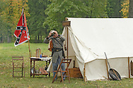 A soldier adjusts his cap in the Confederate camp during a Civil War reenactment hosted by the 124th New York State Volunteers at the Orange County Farmers Museum on Sept. 23, 2006.