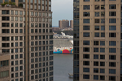 cruise ship on the Hudson River in New York between two apartment buildings