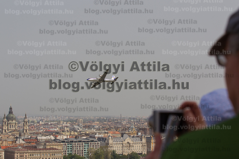 Tourist photographs an airplane fly above the city during an air show above river Danube crossing central Budapest, Hungary on May 01, 2013. ATTILA VOLGYI