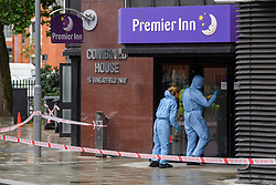 © Licensed to London News Pictures. 21/08/2021. London, UK. Forensic investigators look at a door of a Premier Inn hotel at the scene of a fatal stabbing in Kingston. Police were called to a disturbance on Clarence Street at 03:45BST where they found a 22-year-old male with a stab injury to the chest, he was taken to hospital by London Ambulance Service where he was pronounced dead. An 18-year-old male was arrested at the scene on suspicion of murder.Photo credit: Peter Manning/LNP