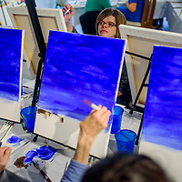 Jennifer Jaggi and others participate in a wine and painting class at Art123 Gallery in downtown Gallup Thursday. GallupArts sponsors monthly the class where students learning painting techniques while drinking wine and socializing.