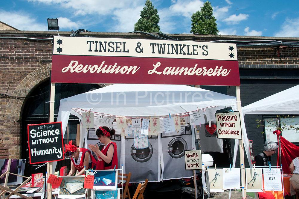 Buxton Street off Brick Lane, East London. June 8th 2014. Vauxhall Art Car Boot Fair. Tinsel and Twinkle's Revolution launderette.
