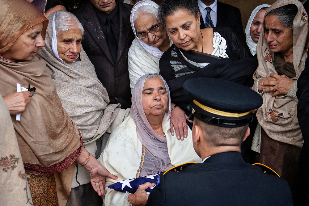 Lodi, California   2014<br /> A military honor guard presents Sukwinder Kaur with the American flag that had draped the coffin of her son. Parminder Singh Shergill, 43, who served in the US Army during the first Gulf War and struggled with mental illness, was shot by police near his home. Officers responding to a 911 call claimed he lunged at them with a knife. Witnesses disputed the police account. An investigation cleared the officers of wrongdoing. Shergill was buried with military honors.