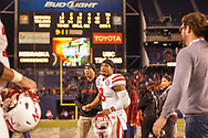 Ameer shakes hands with assistant coach Ron Brown after a 45-42 loss to USC at the Holiday Bowl in San Diego on Dec. 27, 2014, the final game of Abdullah's career. He rushed 27 times for 88 yards and a touchdown. He finished his career as Nebraska's all-time all-purpose yardage leader on 11th  on the NCAA charts with 7,168. © Aaron Babcock