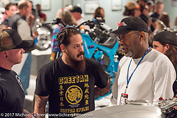Cristian Sosa and Sugar Bear talking at the Old Iron - Young Blood exhibition media and industry reception in the Motorcycles as Art gallery at the Buffalo Chip during the annual Sturgis Black Hills Motorcycle Rally. Sturgis, SD. USA. Sunday August 6, 2017. Photography ©2017 Michael Lichter.