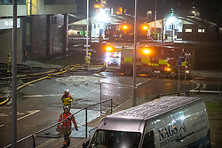 © Licensed to London News Pictures . 01/01/2018. Liverpool, UK. Fire hoses run alongside the entrance to the car park which runs underneath an apartment block . Scene at the Liverpool Echo Arena car park where firefighters are working to extinguish a fire that started late on New Year's Eve and that destroyed all 1,400 cars parked in the multi-story car park. The Liverpool International Horse Show taking place at the Arena was abandoned and people and horses evacuated as dozens of fire crew worked to control the blaze . Photo credit: Joel Goodman/LNP
