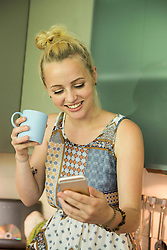 Beautiful young woman looking at smartphone and drinking coffee in the kitchen, Munich, Bavaria, Germany