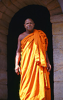 A monk from the lakeside monastery in Kandy emerges through a stone archway.