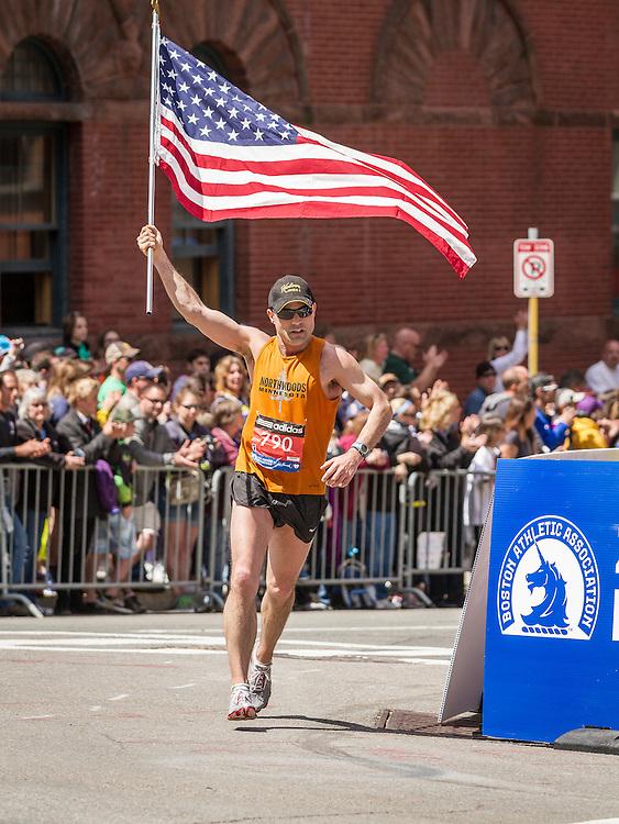 2014 Boston Marathon: runner carries American flag onto Boylston Street