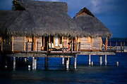 A vacation hut sits on top of the blue waters of Tahiti