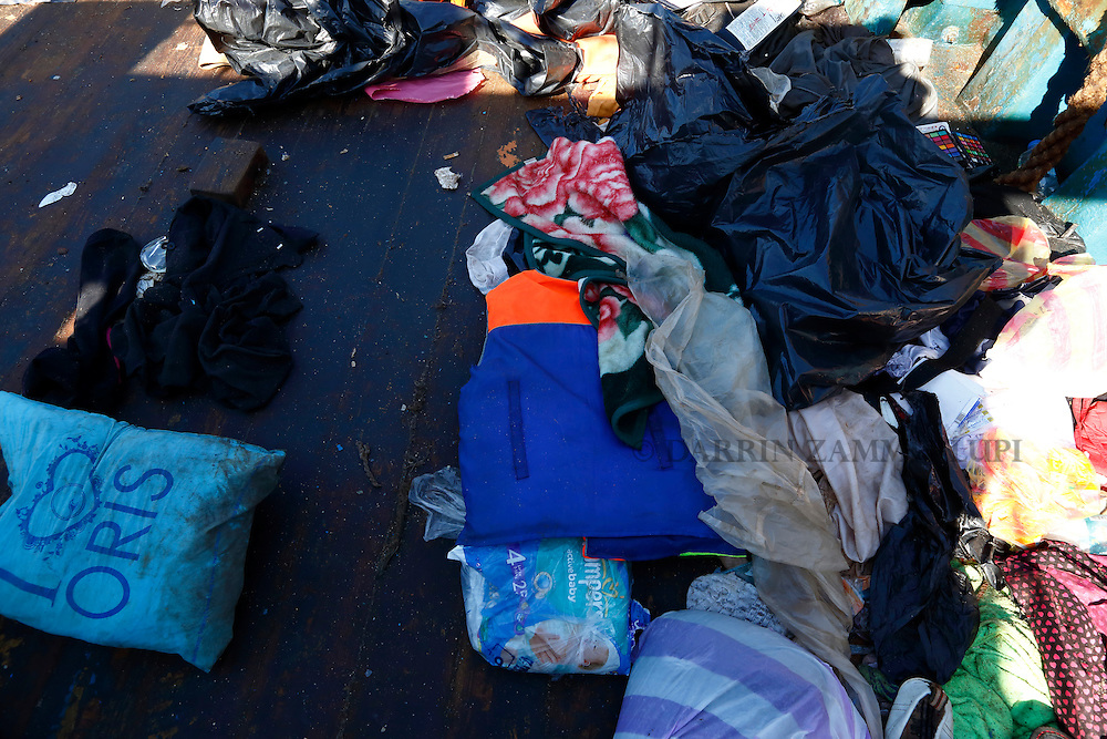 Migrants' belongings and a life jacket litter the deck of a wooden boat from which migrants were rescued 10.5 miles (16 kilometres) off the coast of Libya August 6, 2015.  An estimated 600 migrants on the boat were rescued by the international non-governmental organisations Medecins san Frontiere (MSF) and the Migrant Offshore Aid Station (MOAS) without loss of life on Thursday afternoon, according to MSF and MOAS, a day after more than 200 migrants are feared to have drowned in the latest Mediterranean boat tragedy after rescuers saved over 370 people from a capsized boat thought to be carrying 600.<br /> REUTERS/Darrin Zammit Lupi <br /> MALTA OUT. NO COMMERCIAL OR EDITORIAL SALES IN MALTA