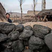 Ding Nanyu, stands behind her neighbor's coal pile. Ms. Ding's husband was killed in a mining disaster. Government officials describe safety conditions in small mines, like where Ms. Ding's husband perished, as grim. Although the number of mine accidents has improved dramatically over the past decade, a Chinese miner is still 10 times more likely to die than a miner from other developed nations.