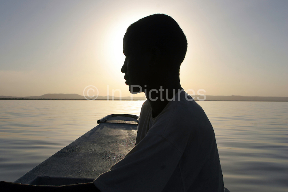 A herdsman travels across the lake on a boat. The Turkana herdsmen have had to change their traditional way of living as pastoralists and learn new skills. Some of the younger men have become fishermen on Lake Turkana.