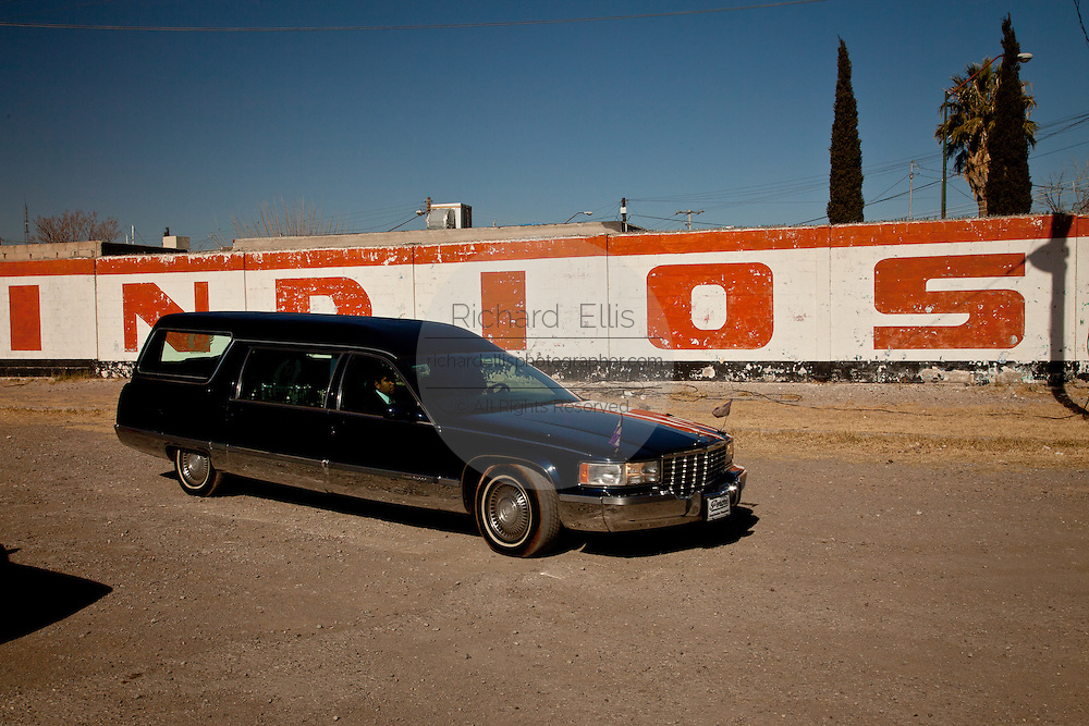 The hearse carrying slain baseball player Jaime Irigoyen, passes the team sign at the Juarez Indios baseball stadium, following a memorial service for the slain youth in Juarez, Mexico January 16, 2009. Irigoyen, 19-year-old, was reportedly grabbed by the military from his home and found executed the neat mourning. An ongoing drug war has already claimed more than 40 people since the start of the year. More than 1600 people were killed in Juarez in 2008, making Juarez the most violent city in Mexico.    (Photo by Richard Ellis)