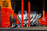 Pedestrian walking past graffiti wall on construction hoarding in Great Eastern Street East London. This image The Queens Guard by the artist Ives One based in Amsterdam.
