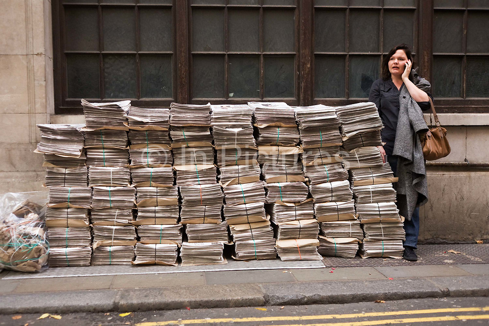 Stacks of Evening Standard newspapers are piled in a side street near Holborn station as a commuter makes mobile phone call. Awaiting collection by a team of vendors who will take them to various local locations and hand them out for free to passing commuters, the stacks have been placed against a wall in the side-street. The woman who has paused in her journey home stands with her coat hanging from her shoulder and her bag hooked at her elbow, as she speaks into her mobile (cell) phone.