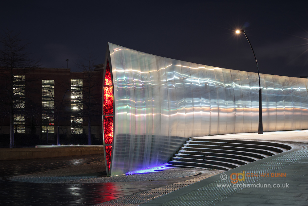 Glowing glass at the end of the Cutting Edge sculpture punctuates this night scene at Sheaf Square in Sheffield. An urban landscape of light, lines and curves in South Yorkshire, England, UK.