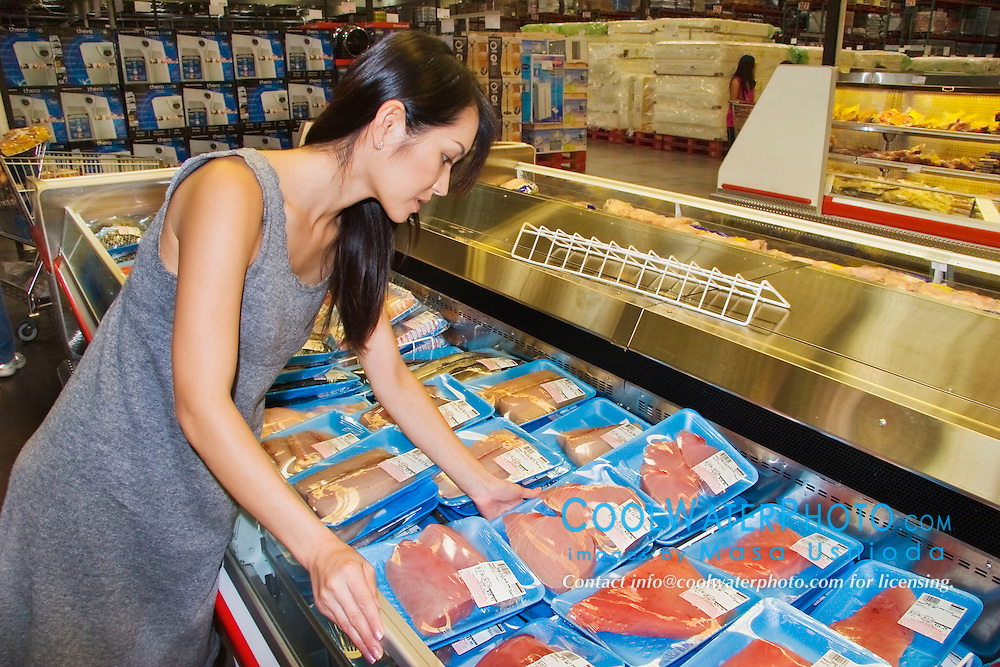 woman shopper choosing neatly packaged fresh fillet steaks of Pacific blue marlin meat for sale at supermarket in Kailua Kona, Big Island of Hawaii, Makaira nigricans, imported from F.S.M. - Federated States of Micronesia