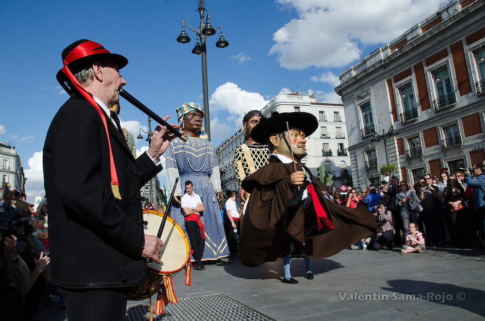 Male 'Gigantillo' dancing at Puerta del Sol square of Madrid during San Isidro 2013 parade while a man plays a flute and a drum.