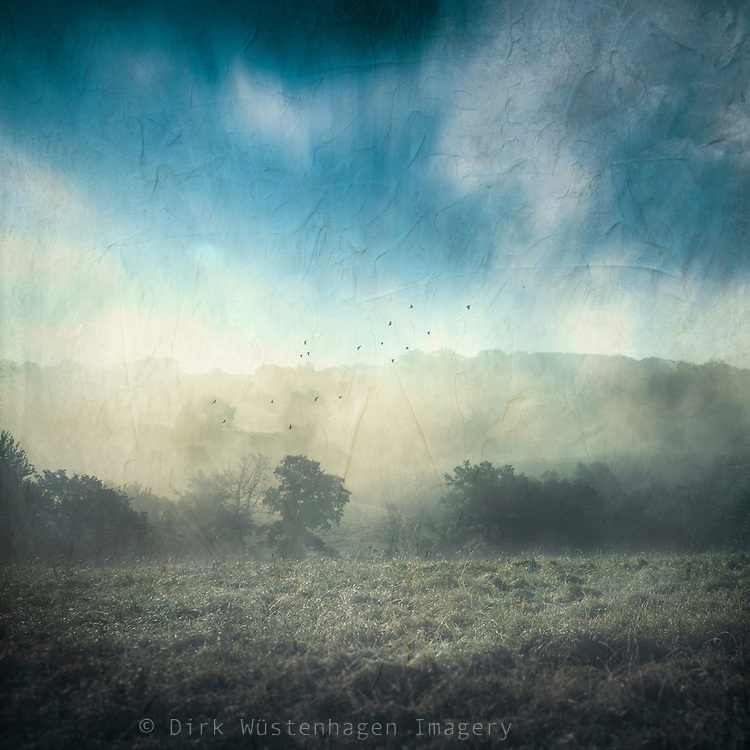 clouds and rising fog on a fall morning - texturized photograph