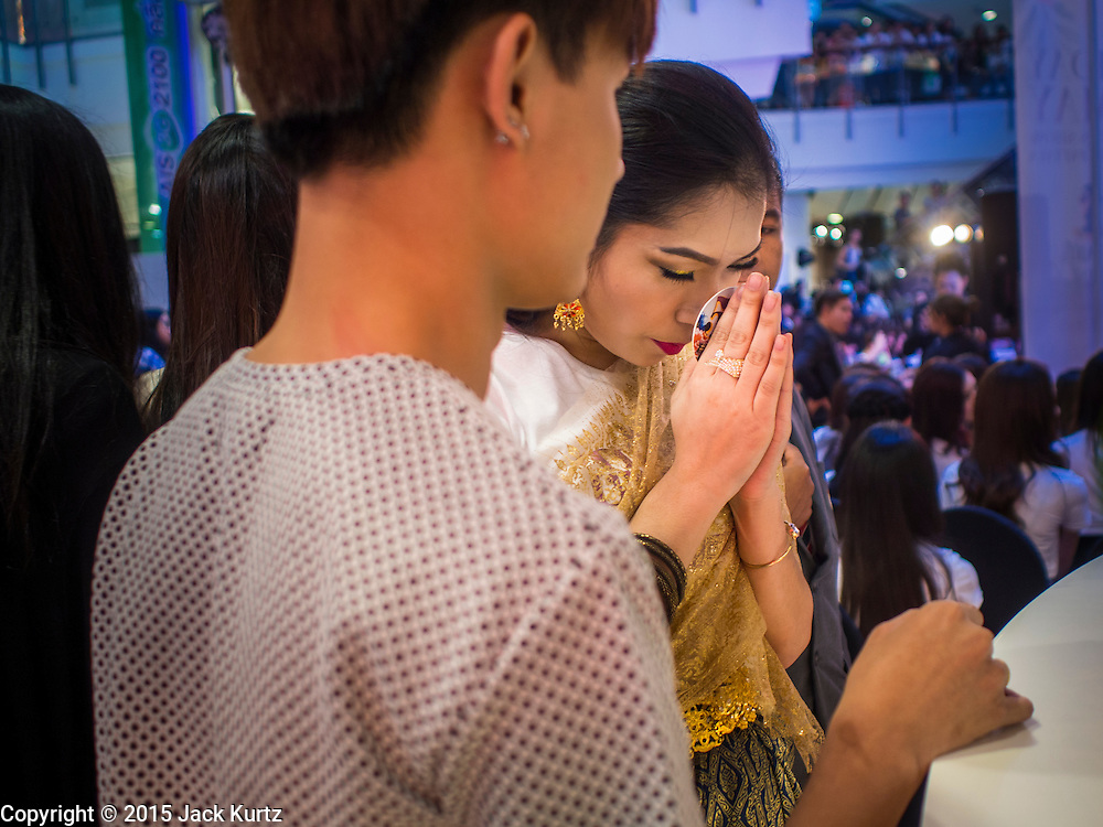 25 MARCH 2015 - BANGKOK, THAILAND:  Contestants pray before going on stage in the first round of the Miss Tiffany's contest at CentralWorld, a large shopping mall in Bangkok. Miss Tiffany's Universe is a beauty contest for transgender contestants; all of the contestants were born biologically male. The final round will be held on May 8 in the beach resort of Pattaya. The final round is televised of the  Miss Tiffany's Universe contest is broadcast live on Thai television with an average of 15 million viewers.     PHOTO BY JACK KURTZ