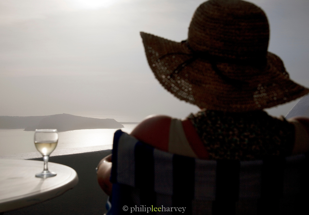 Woman with a glass of wine on a terrace balcony overlooking a bay in Imerovigli, balcony to the Aegean, an area in Fira village, Santorini, Greece