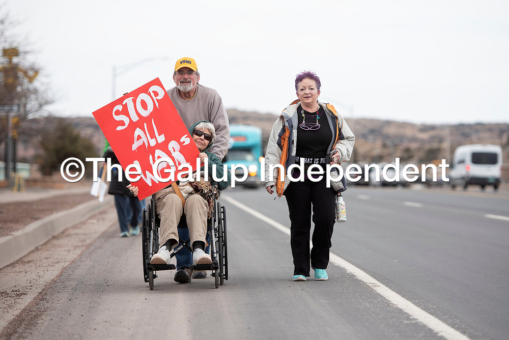 """Larry Winn pushes Jessie Orphey in a wheelchair while she holds a """"Stop All Wars"""" sign as they make their way down Montoya Boulevard accompanied by Colleen Procopio to the Larry Brian Mitchell Recreation Center for a tribute to Martin Luther King, Jr. Monday afternoon in Gallup."""