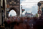 "Huge amounts of mostly visitors   moving across a traffic light to the beginning of Charles Bridge and towards ""Lesser Town"" (Mala Strana) and Prague Castle."