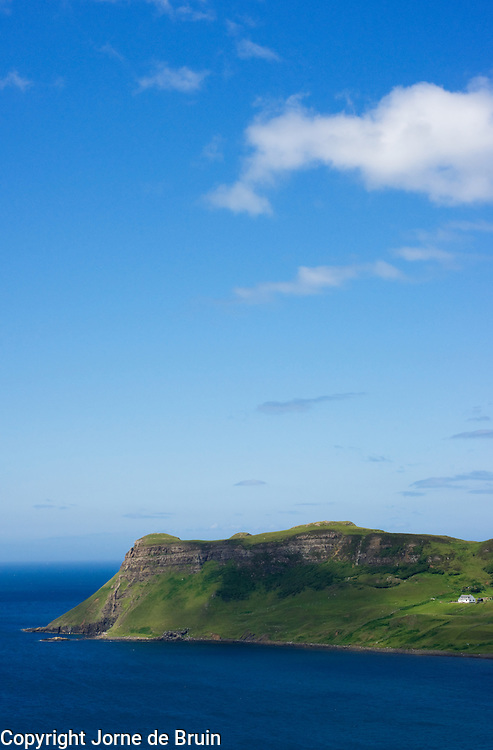 A white house on a cliff above the blue sea and against a blue sky Isle of Skye, Scotland, UK.