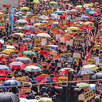 A sea of protesters during June protests in Hong Kong. Signs are interspersed between colorful umbrellas as thousands march in Central Hong Kong. Protesters are opposed to a controversial extradition bill.