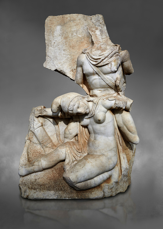 Roman Sebasteion relief sculpture of Nero conquering Armenia Aphrodisias Museum, Aphrodisias, Turkey.  Against a grey background.<br /> <br /> Nero, wearing only a cloak and sword strap, supports a slumped naked Armenia by her upper arms. She wears a soft eastern hat, and her bow and quiver are next to her. The heroic composition likens them to Achilles and the Amazon Queen Penthesilea. The inscription reads: Armenia - (Neron) Klaudios Drousos Kaisar Sebastos Germanikos. .<br /> <br /> If you prefer to buy from our ALAMY STOCK LIBRARY page at https://www.alamy.com/portfolio/paul-williams-funkystock/greco-roman-sculptures.html . Type -    Aphrodisias     - into LOWER SEARCH WITHIN GALLERY box - Refine search by adding a subject, place, background colour, museum etc.<br /> <br /> Visit our ROMAN WORLD PHOTO COLLECTIONS for more photos to download or buy as wall art prints https://funkystock.photoshelter.com/gallery-collection/The-Romans-Art-Artefacts-Antiquities-Historic-Sites-Pictures-Images/C0000r2uLJJo9_s0