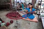 Nepalese female worker of the R.C Rug Factory in the Narayanthan area of Kathmandu, Nepal.  She is using a spinning device to wrap the wool up into balls. The R.C Rug Factory export to Europe, U.S and Canada; and rely on the Good Weave certificate of approval to boast excellent quality and fair conditions for its workers. This is because the carpet factory industry in Nepal is notorious for providing poor working conditions and forcing young children into labour.