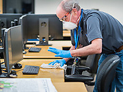 """19 MARCH 2020 - DES MOINES, IOWA:  HOWARD HENRY, a worker for the Des Moines Public Schools, cleans a computer arts classroom at Central Campus, a high school in the Des Moines Public Schools system. Des Moines schools are closed for at least 30 days because of the coronavirus and officials are using the time to """"deep clean"""" and sanitize each school. On Thursday morning, 19 March, Iowa reported 38 confirmed cases of the Coronavirus. Restaurants, bars, movie theaters, places that draw crowds are closed for at least 30 days. There are no """"shelter in place"""" orders in effect anywhere in Iowa but people are being encouraged to practice """"social distancing"""" and many businesses are requiring or encouraging employees to telecommute.      PHOTO BY JACK KURTZ"""