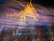 "04 MARCH 2015 - BANGKOK, THAILAND:  A time exposure of monks and people participating in a procession around the ""wiharn,"" or prayer hall, at Wat Benchamabophit on Makha Bucha Day. Makha Bucha Day is an important Buddhist holy day and public holiday in Thailand, Cambodia, Laos, and Myanmar. Many people go to temples to perform merit-making activities on Makha Bucha Day. Wat Benchamabophit is one of the most popular Buddhist temples in Bangkok.   PHOTO BY JACK KURTZ"