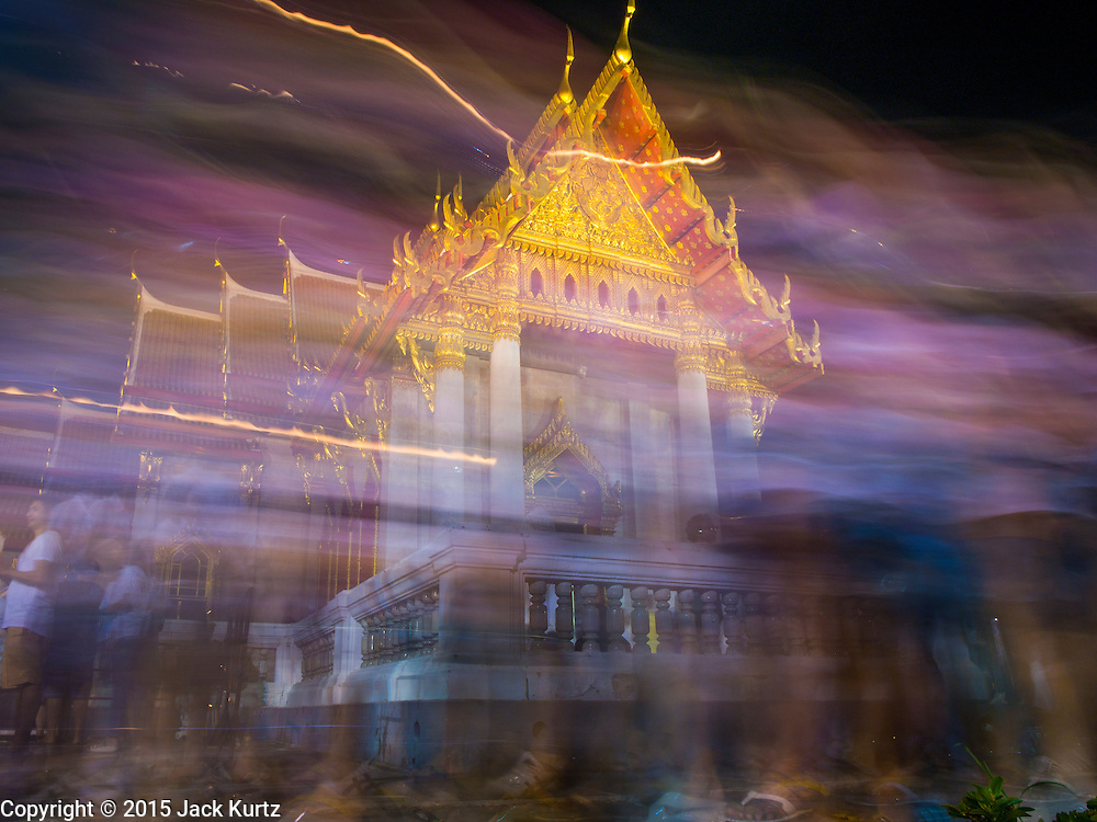 """04 MARCH 2015 - BANGKOK, THAILAND:  A time exposure of monks and people participating in a procession around the """"wiharn,"""" or prayer hall, at Wat Benchamabophit on Makha Bucha Day. Makha Bucha Day is an important Buddhist holy day and public holiday in Thailand, Cambodia, Laos, and Myanmar. Many people go to temples to perform merit-making activities on Makha Bucha Day. Wat Benchamabophit is one of the most popular Buddhist temples in Bangkok.   PHOTO BY JACK KURTZ"""