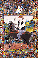 Tombstone showing a man on his horse, The  Merry Cemetery ( Cimitirul Vesel ),  Săpânţa, Maramares, Northern Transylvania, Romania.  The naive folk art style of the tombstones created by woodcarver  Stan Ioan Pătraş (1909 - 1977) who created in his lifetime over 700 colourfully painted wooden tombstones with small relief portrait carvings of the deceased or with scenes depicting them at work or play or surprisingly showing the violent accident that killed them. Each tombstone has an inscription about the person, sometimes a light hearted  limerick in Romanian. .<br /> <br /> Visit our ROMANIA HISTORIC PLACXES PHOTO COLLECTIONS for more photos to download or buy as wall art prints https://funkystock.photoshelter.com/gallery-collection/Pictures-Images-of-Romania-Photos-of-Romanian-Historic-Landmark-Sites/C00001TITiQwAdS8