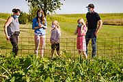 27 AUGUST 2020 - LACONA, IOWA: THERESA GREENFIELD, left, looks at the Jordan family garden with BETH JORDAN, JANELLE JORDAN, 8, LAURA JORDAN, 11, and JUSTIN JORDAN. Greenfield, a Democrat, is running against Republican US Senator Joni Ernst to represent Iowa in the US Senate. Greenfield toured the Jordan Farm in Lacona and talked about her rural policies, including plans to bring hi speed internet to rural areas.    PHOTO BY JACK KURTZ
