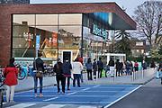 Nederland, Nijmegen, 10-4-2020  Bij een vestiging van Alber Heijn staan mensen in de rij om in de winkel hun boodschappen te doen . Er mag een beperkt aantel klanten binnen zijn en een medewerkster houdt dat in de gaten . De bezoekers moeten een winkelwagentje meenemen . Foto: Flip Franssen