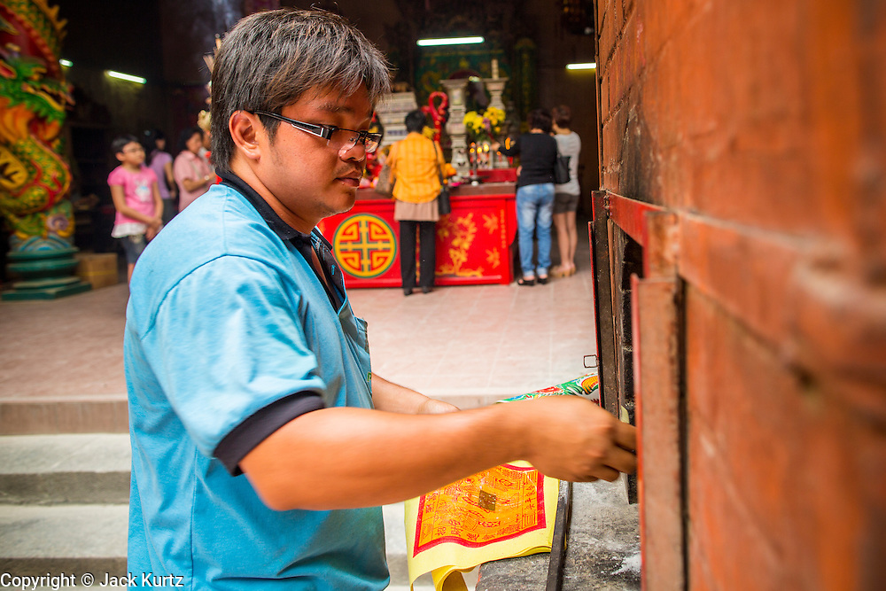 20 DECEMBER 2012 - KUALA LUMPUR, MALAYSIA: A man burns offerings in a kiln at the Guan Di Temple in Kuala Lumpur, Malaysia. Guan Di Temple (God of War Temple) was built in 1888 and is one of the oldest Chinese Temples in Kuala Lumpur.   PHOTO BY JACK KURTZ