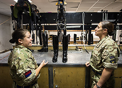© London News Pictures. 14/07/2015.  Sergeant and WO2 Rachael Ballard inspect the Gunners kit before they put it on. . More usually associated with the ceremonial gun salutes and musical rides with their 13lb guns, they took on the role of both mounted and dismounted guard at the entrance of Horse Guards. This year, for the first time, they are using Knightsbridge Barracks, the home of the Household Cavalry Mounted Regiment, for the period of their duty, as opposed to Wellington Barracks, which they have used in previous years.  Photo credit: Sergeant Rupert Frere/LNP