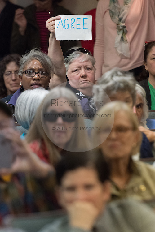 """A member of the audience holds up a sign with the word """"Disagree"""" during a heated discussion with U.S. Sen. Tim Scott and U.S. Rep. Mark Sanford at a town hall meeting February 18, 2017 in Mount Pleasant, South Carolina. Hundreds of concerned residents turned up for the meeting to address their opposition to President Donald Trump during a vocal meeting held by U.S. Rep. Mark Sanford and Senator Tim Scott."""