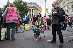 London, UK. 23rd August, 2021. An environmental activist from Extinction Rebellion sits on a chair in the road in Trafalgar Square during the first day of Impossible Rebellion protests. Extinction Rebellion are calling on the UK government to cease all new fossil fuel investment with immediate effect. Credit: Mark Kerrison/Alamy Live News