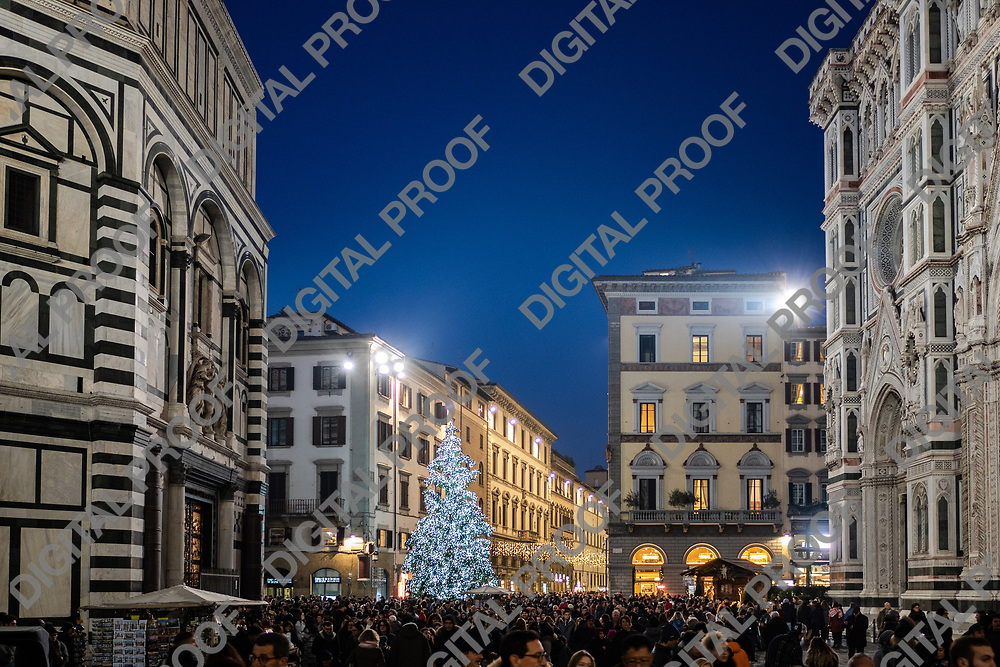 Firenze, Tuscany Italy - December 30, 2018 Florence Christmas Tree Lights with tourist crowd, Florence Duomo at right and St John's Baptestry at left, dusk time